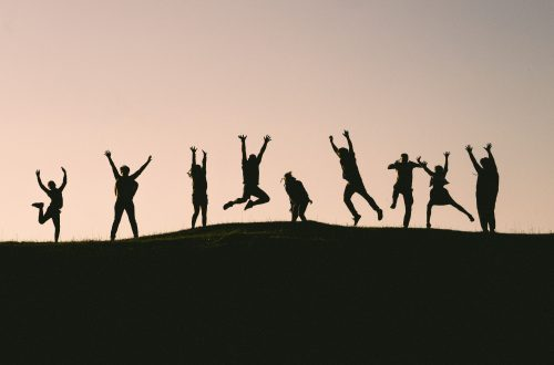 Silhouette of a group of friends celebrating something.
